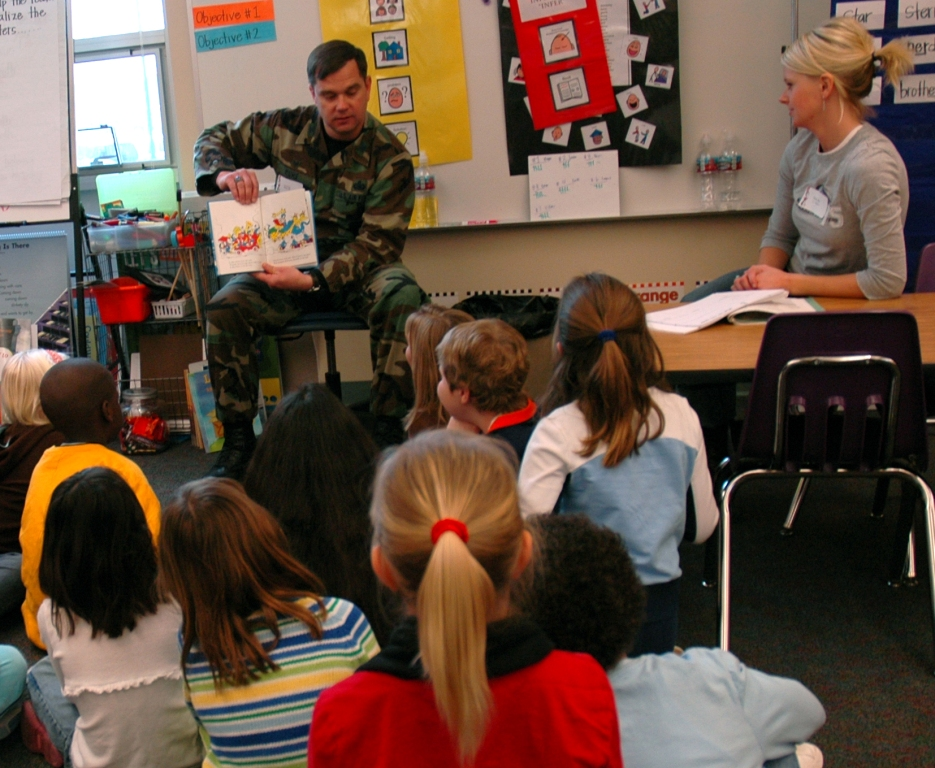 "Col. Steven Muhs, 460 Mission Support Group commander, reads ""And to Think that I saw it on Mulberry Street"" to a group of first and second graders at Murphy Creek K - 8."