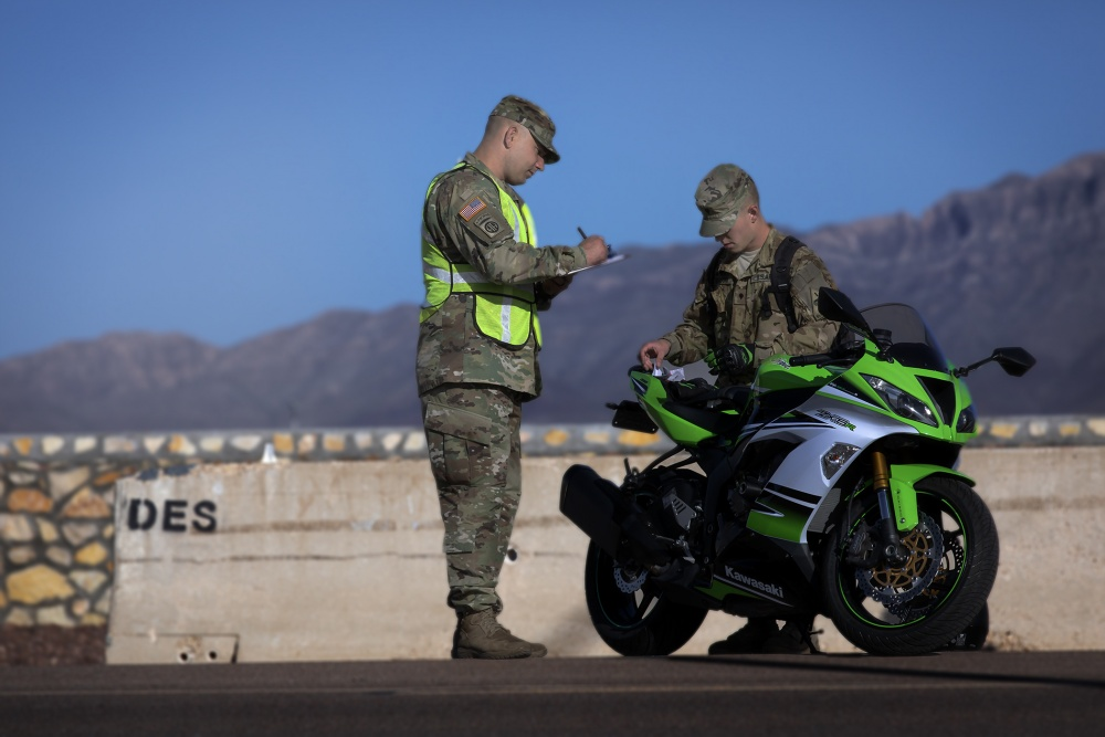 Chief Warrant Officer 3 Steven Drakes, from the 1st Armored Division G-4, reviews a motorcycle safety inspection list with a Soldier-rider on East Fort Bliss. Fort Bliss, Texas.
