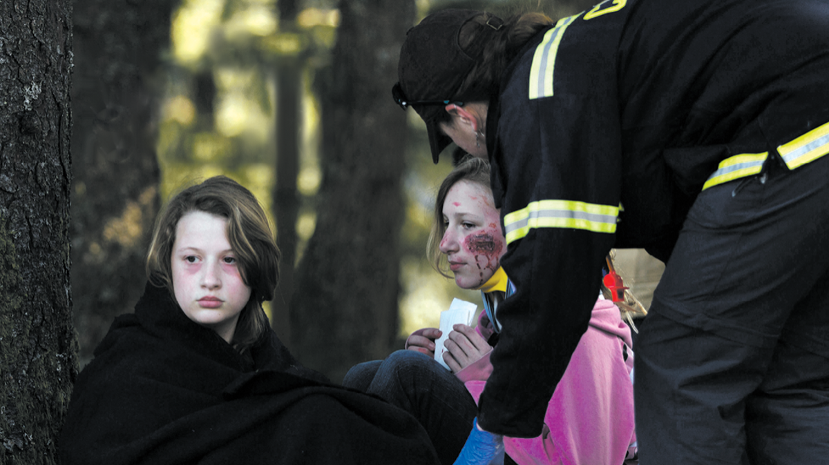 Injured victims receiving assistance from first responder, Joint Base Elmendorf-Richardson, JBER