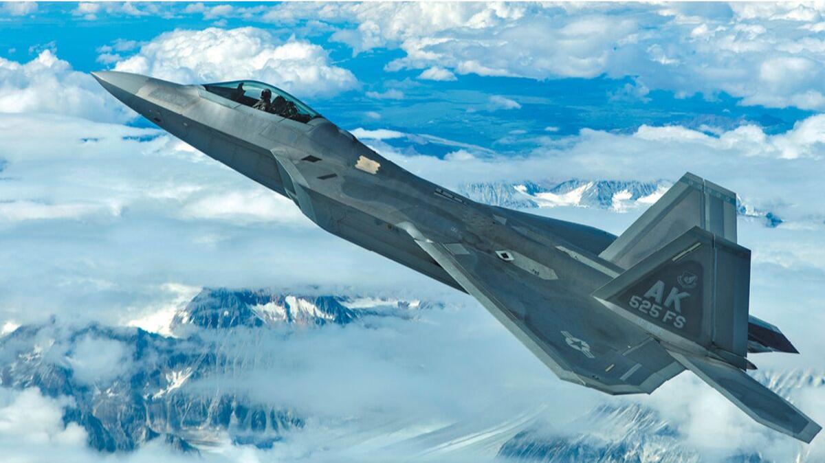 F-22 jet in flight over snow covered mountains, Joint Base Elmendorf-Richardson, JBER