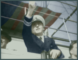 Colorized still of LCDR James Hughes shortly before the attack. Note the large US flag tied down flat above him.