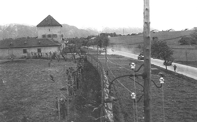 A firefight erupts outside of the Murnau POW camp between American and Nazi soldiers. Prisoners in the camp are seen running towards or away from the barbed wire fence.