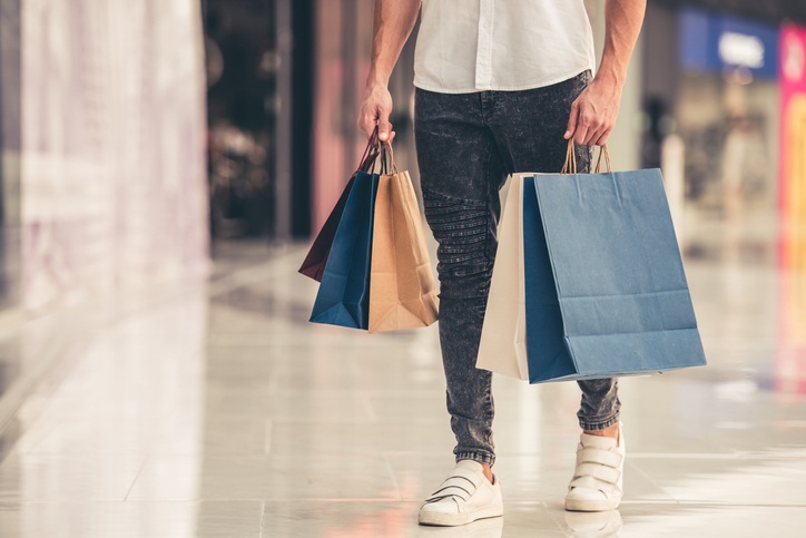 Cropped image of handsome guy with shopping bags doing shopping in the mall