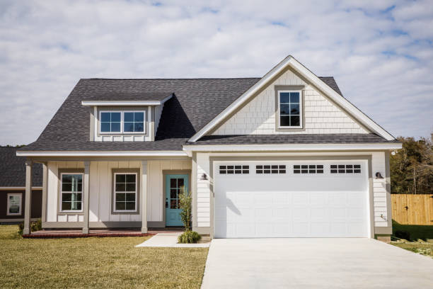 This three bedroom house was just built and it includes a spacious kitchen with stainless steel appliances, a large whote marble countertop, a custom white plank shiplap style fireplace with a custom mantle and dark wood floors. It is a one story house with modern finishes and an open floorplan. It includes a wide driveway, a garage and a back porch.