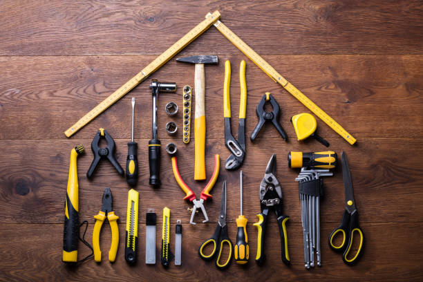 Elevated View Of Many Tools With Roof Made With Yellow Measuring Tape On Wooden Table