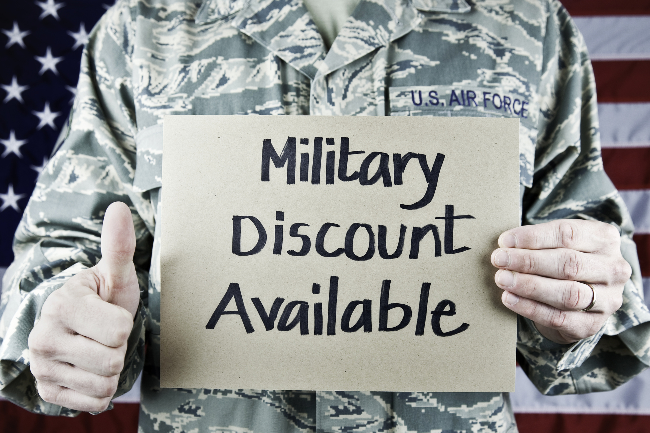 US soldier holding sign Military Discount AvailableUniform is the newest in regulation.